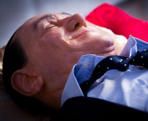Berlusconi defunto in mostra a pochi metri da Palazzo Chigi. In una teca e con le scarpe di Topolino