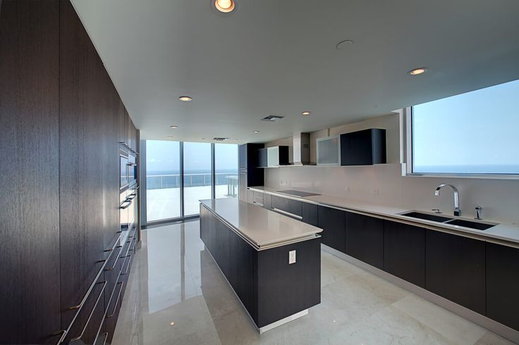 Long, open space here is punctuated by large dark wood and white countertop island, matching the cabinetry and countertops in the rest of the kitchen. Light marble flooring reflects ample sunlight via floor to ceiling windows.