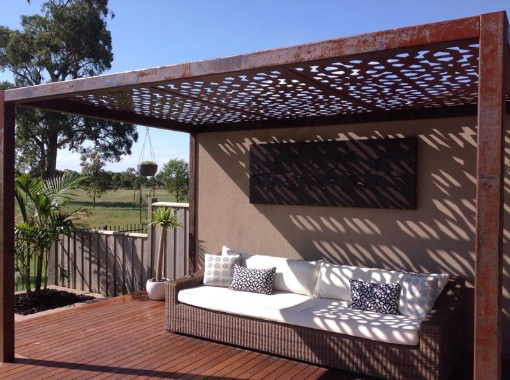 Outdoor alfresco living area with laser cut roofing panels and pergola structure by Entanglements in a rusty finish. Create interesting wall shadows with this geometric screening design