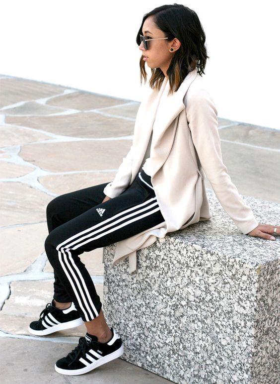 6 tipos de calças queridinhas entre as fashion girls. Blazer rosa, t-shirt branca, calça esportiva preta com listras nas laterais, tênis preto adidas