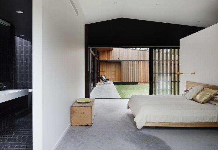 Stile minimalista ed eleganza discreta per la camera da letto padronale, posta a fianco del living all'interno della Hover House. La vetrata si apre sulla corte centrale, in continuità con la veranda in cemento