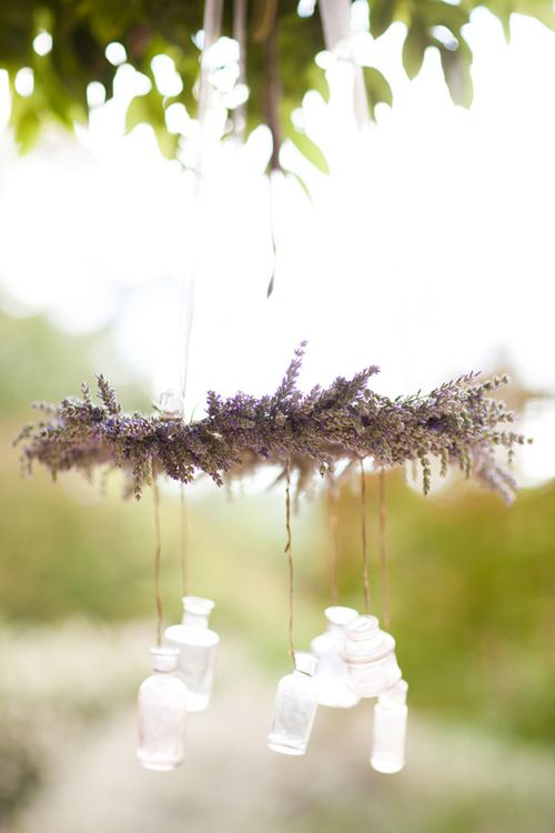 chandelier was made by tying lavender bundles around a french pastry cooling rack and then hanging antique lavender bottles from the rack