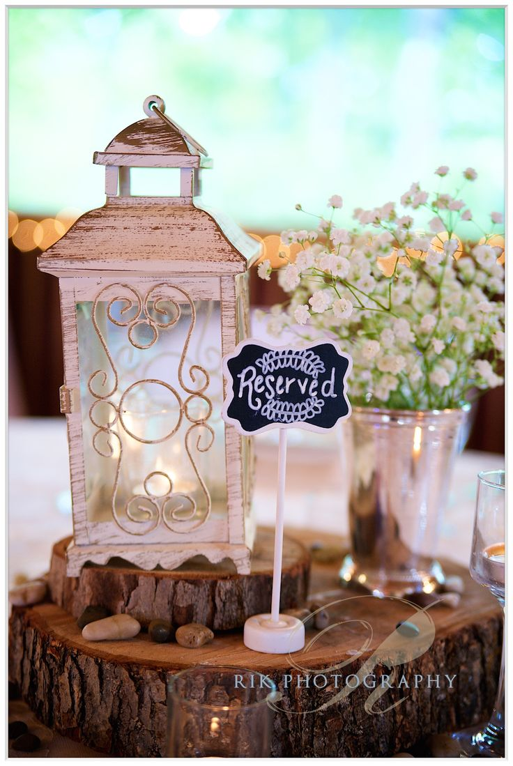 Centerpieces. White lanterns on wooden slabs with baby's breath. Bluff Mountain Inn