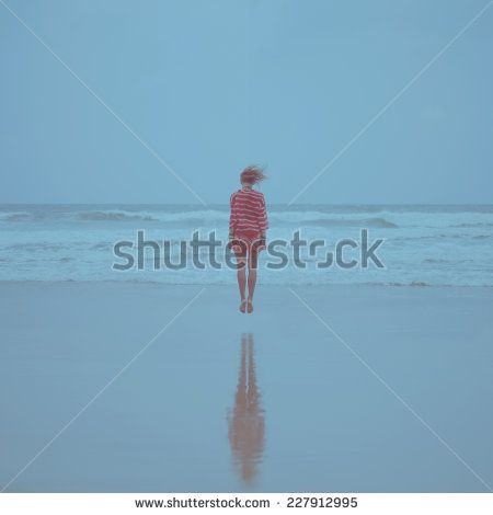 girl floating in the air above the waves on the beach near the sea