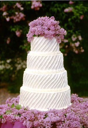 flowers at bottom of wedding cake, Lilacs are great for a cake as they are safe and edible, unlike hydrangea