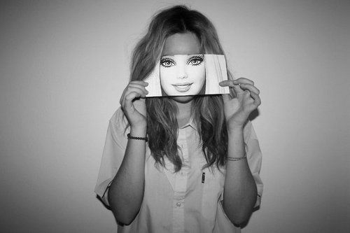 An image of a girl holding up a photo of the face of a Barbie doll. I love this…