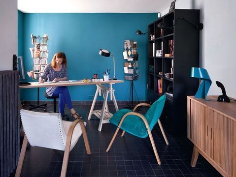 Le bureau de Sophie aux accents rétro et scandinaves mêle le bleu canard (réédition des années 60 « Marine Blue » Little Green) et le bois. On aime les jolis fauteuils, le bureau fait de tréteaux et les anciens portes cartes postales chinés qui servent de matériauthèque.