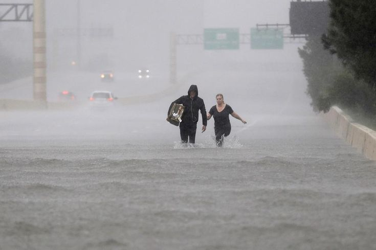 In the US city of Houston, George Cochrum and Caroline Wheeler walk down the flooded roads of Interstate 610 in the aftermath of Hurricane Harvey.