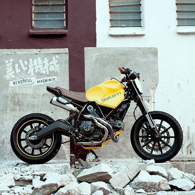 The lads from @beautiful_machines_malaysia were given a Ducati Scrambler with a botched custom job to repair.  They went hard out to revamp the bike, and this is the result—with the brilliant name 'Dirty Fellow.' It's got a hybrid tracker/scrambler stance to exploit the Duc's built-in fun factor. The rear subframe is a one-off unit that trims about six inches of heft from the back end, and allows an intricate re-routing of the custom exhaust.  The tank is a completely custom unit—scalloped…