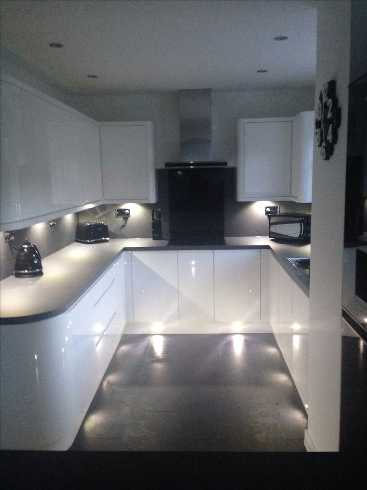 White gloss handless wren kitchen with curves, grey slate work top and flooring, tech wall