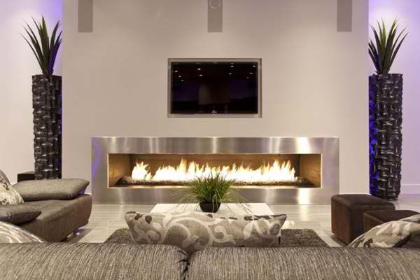 Amazing TV above fireplace accented by stone columns with plants.