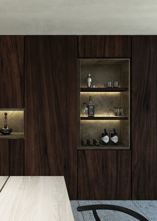 Interior design for a kitchen remodelling in an existing private residence. Featuring a sculptural kitchen island in black Nero Marquina marble. The facetted shape of the island is framed in a bronze geometric grid. The cooking niche, with a patinated bronze backsplash, is hidden behind floor-to-ceiling cupboard doors in Travertine.