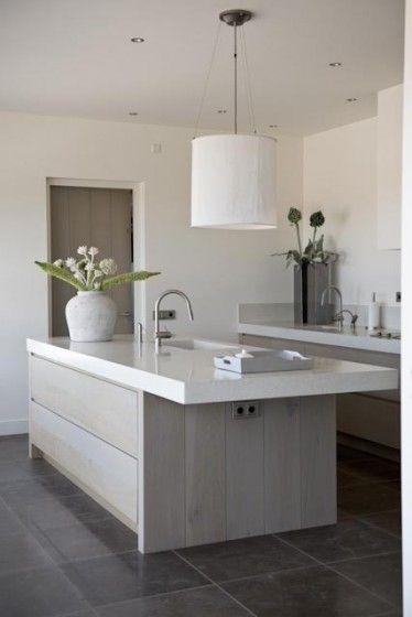 cocina abierta con isla central para fregadero, muebles madera color natural, sin muebles altos y campana de obra