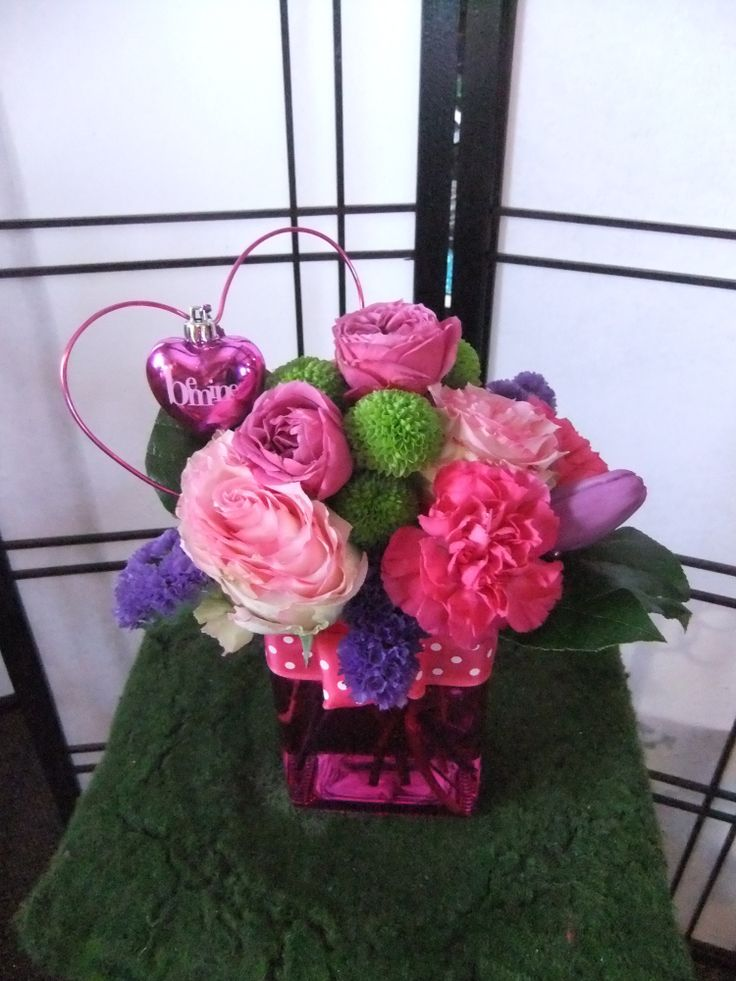 Be Mine-tall pink cube, 5 pink carnations, 2 esperance roses, kermits, purple statice, salal, pink spray rose, purple tulip, pink hearts with polka dot ribbon