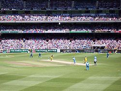 An ODI match between India and Australia in January 2004. The men wearing black trousers are the umpires. Teams in limited overs games, such as ODIs and T20s, wear multi-coloured uniforms and use white cricket balls.