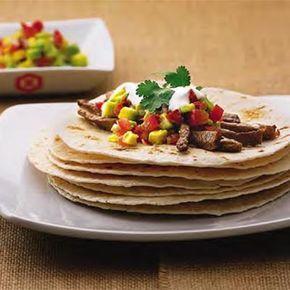 Couper l'avocat en petits dés, les mettre dans un saladier avec le jus de citron vert. Couper les tomates en dés. Les ajouter à l'avocat. Couper en petits dés fins les piments. Eplucher l'oignon et le ciseler. Mélanger les piments, l'oignon, le vert de la coriandre et 4 cuillères à soupe de marinade Teriyaki avec les tomates et l'avocat. Couvrir et laisser macérer deux heures à température ambiante avant de servir. Couper la viande en lanières d'un bon demi-centimètre d'épaisseur dans le…