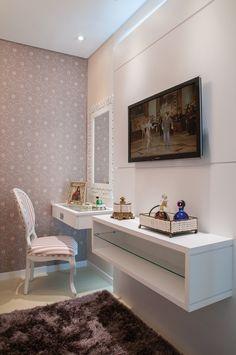 Ao lado da TV, a designer projetou um espaço que recebeu uma penteadeira, acompanhada por uma poltrona em madeira estofada com estampa compondo com o papel de parede. No hall que dá acesso ao quarto, o roupeiro com portas em espelho garante amplitude à entrada. Mais