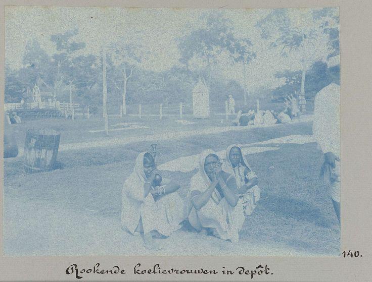 anoniem | Rookende koelievrouwen in depôt, attributed to Hendrik Dooyer, 1906 - 1913 | Enkele vrouwen roken (een soort pijp) zittend op de grond, in het zgn. koeliedepot te Paramaribo. Onderdeel van het fotoalbum Souvenir de Voyage (deel 5), over het leven van de familie Dooyer in en rond de plantage Ma Retraite in Suriname in de jaren 1906-1913.