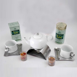 Deluxe Tulsi Tea Gift Set -- Includes: A 100 gm tin and a 25 tea bag box of your choice of ORGANIC INDIA Tulsi Tea, together with a dazzling 10 piece tea set: A beautiful porcelain tea kettle, a stainless steel tea warming stand, two porcelain cups, two stainless steel saucers, two stainless steel spoons and two organic candles. Choose any ORGANIC INDIA Tulsi Tea - Original Tulsi, Tulsi Ginger, Tulsi Green Tea or Tulsi Chai Masala