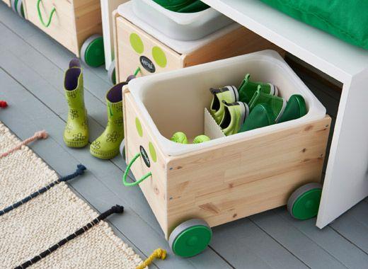 Contenitore in legno decorato con rotelle sotto una panca bianca per riporre le scarpe dei bambini - IKEA
