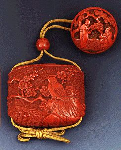 Two-case inro made from cinnabar lacquer finely carved with a continuous scene of pheasants amongst prunus and rockwork against a geometric floral ground, all under a band of clouds; accompanied by matching cinnabar ojime depicting an immortal on a crane and a manju netsuke well-carved in high relief with sages and attendants under a pine tree; signed Murakio with kakihan; Meiji (1868-1912); Japan. 2.25 inches (5.72 cm) long; 2.9 inches (7.37 cm) wide.