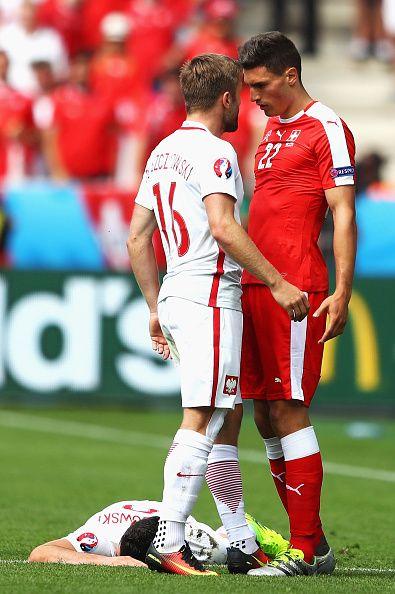 #EURO2016 Fabian Schaer of Switzerland and Jakub Blaszczykowski of Poland argue after Schaer's foul to Robert Lewandowski