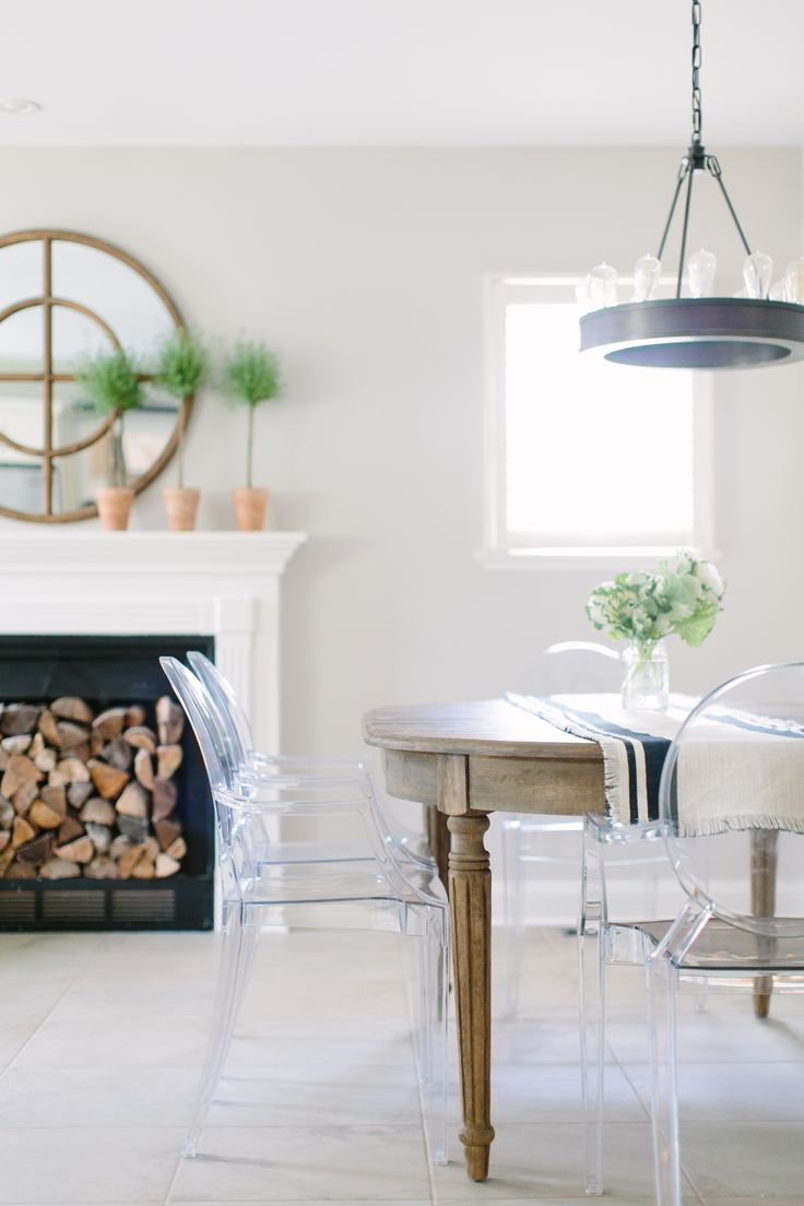 chic breakfast nook is filled with an oval reclaimed wood dining table lined with ghost chairs illuminated by a ralph lauren roark modular ring chandelier