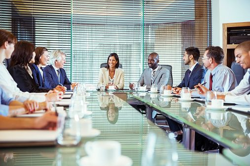 Business people having meeting in in conference room, smiling and discussing