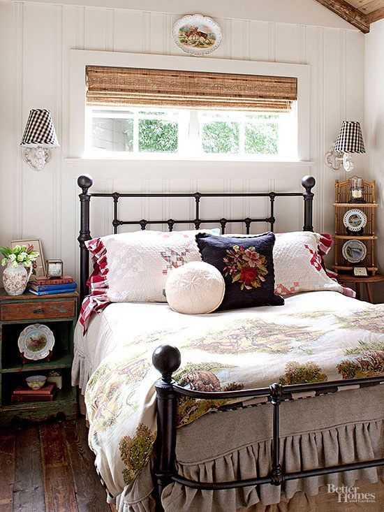An iron bed beckons guests to snuggle under a generous bounty of mismatched linens, including a duvet fashioned from vintage woodland fabric. Buffalo-check lampshades and embroidered pillows add texture to the wood-clad bedroom.