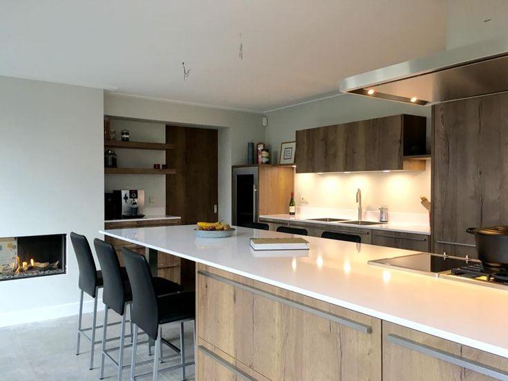 Referentie Wildhagen | Sfeervolle tafel aan het kookeiland en een haard in de keuken.