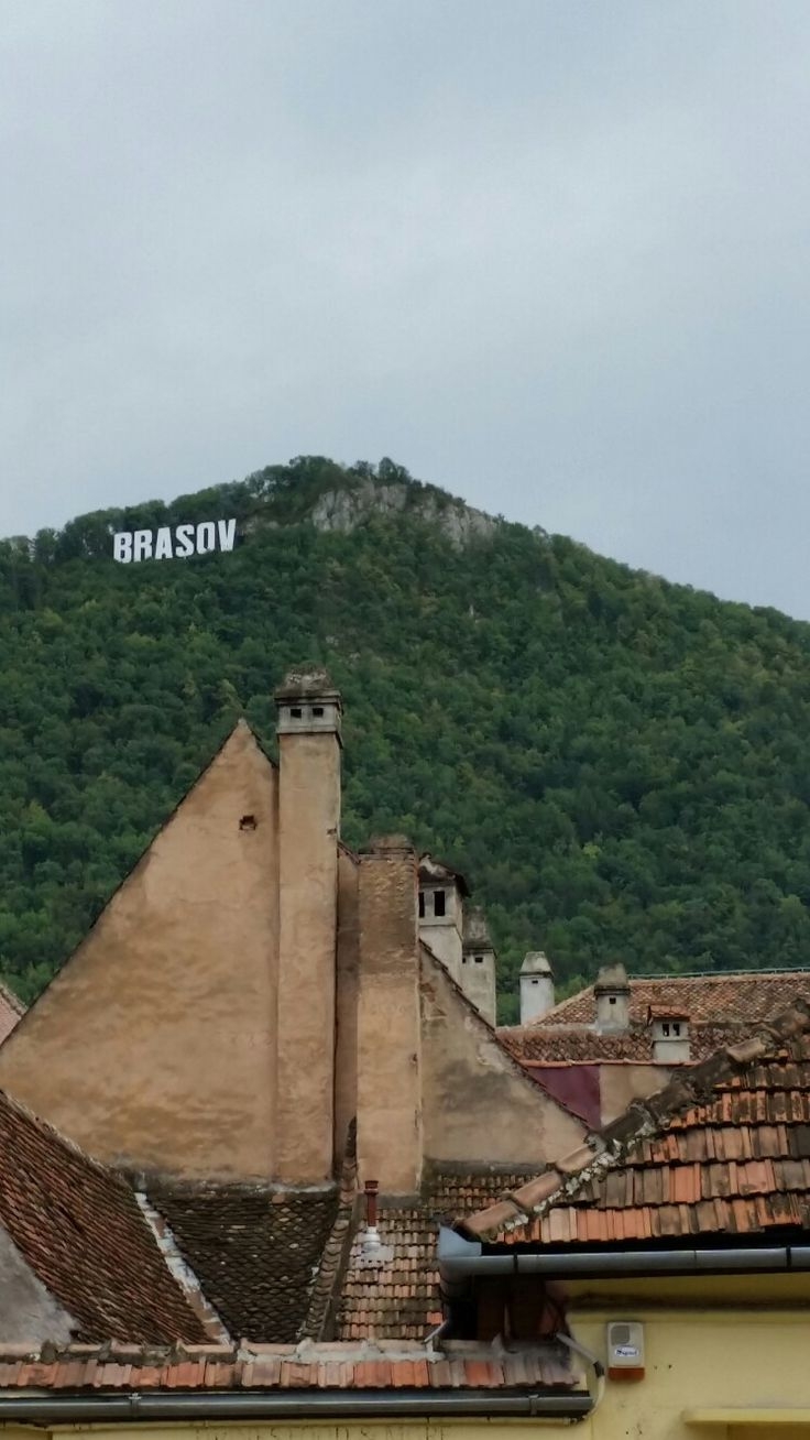 Geometric shape of traditional German houses in Brasov city, Transylvania Romania.  On top of Tampa mountain you can see the name of the city, similar as on Hollywood hills