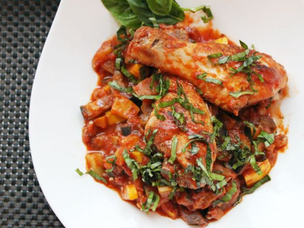 Tender chicken legs are simmered in a fresh summer vegetable ratatouille for this quick one-pot meal.