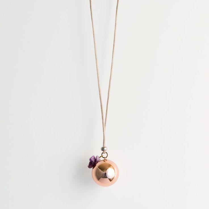 Un joli bola de grossesse d'une belle couleur cuivrée, accompagné de ses pierres en Améthyste. Très joli cadeau à offrir à une femme enceinte et future maman.