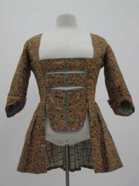 14-11-11  CMU  1750-75  Voor deze caraco (jak) is een sits (katoen bedrukt met bloem- of bladmotief) gebruikt met een bruine achtergrond en een dessin van roze, rode en blauwe bloemen. Dezelfde teint blauw is gebruikt voor de afwerking van het borststuk. Een sitsen jak is een typische Nederlandse kledingvorm.