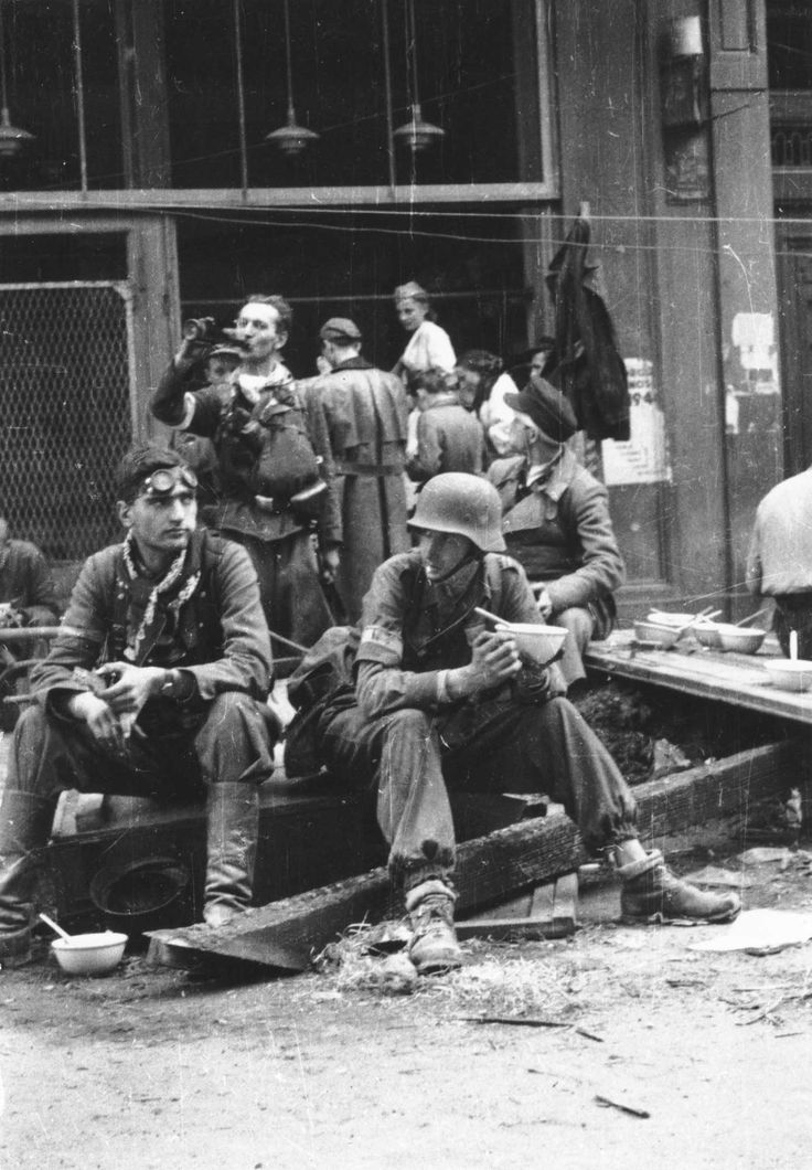 Warsaw Uprising, 1944: Polish Home Army fighters pause for a bite and a drink. Their efforts were eventually brutally quashed by the Waffen SS, with Soviet armies watching from a close distance -- Stalin wanted the Germans to eliminate free-spirited Poles. A large part of Warsaw was completely destroyed as German revenge for the uprising.
