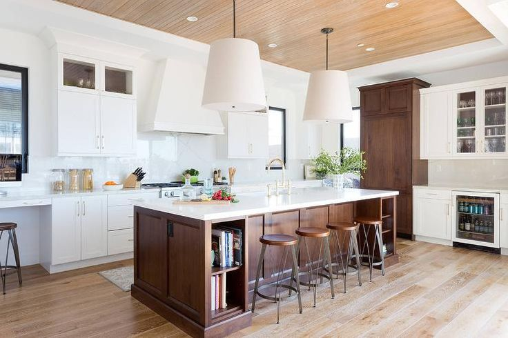 Stunning two toned kitchen boasts a brown oak wainscoted island finished with white quartz countertop fitted with a sink paired with a polished brass deck mount faucet and modular cookbook shelves positioned on either side of metal and wood counter stools lit by Restoration Hardware Barrel Linen Shades hung from a stained oak plank ceiling.