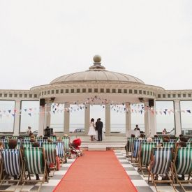 A fabulous wedding set by the British seaside, with deckchairs and the bride and groom taking a paddle in the sea.