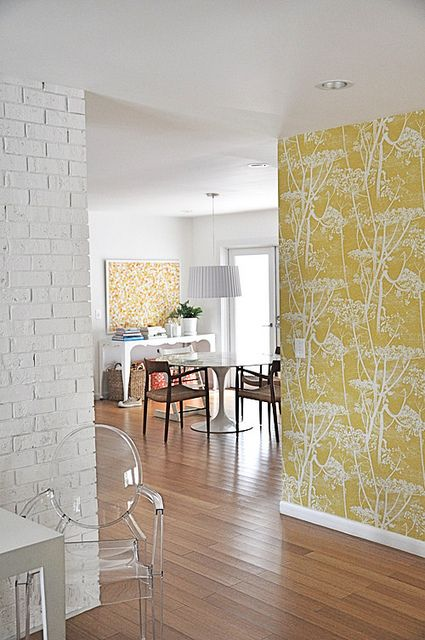 yellow wallpaper in the hall. Preview to next room. notice how they framed the wallpaper in the dining area. love that.