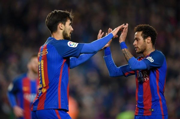 Barcelona's Portuguese midfielder Andre Gomes (L) celebrates with Barcelona's Brazilian forward Neymar after scoring a goal during the Spanish league football match FC Barcelona vs Valencia CF at the Camp Nou stadium in Barcelona on March 19, 2017. / AFP PHOTO / LLUIS GENE