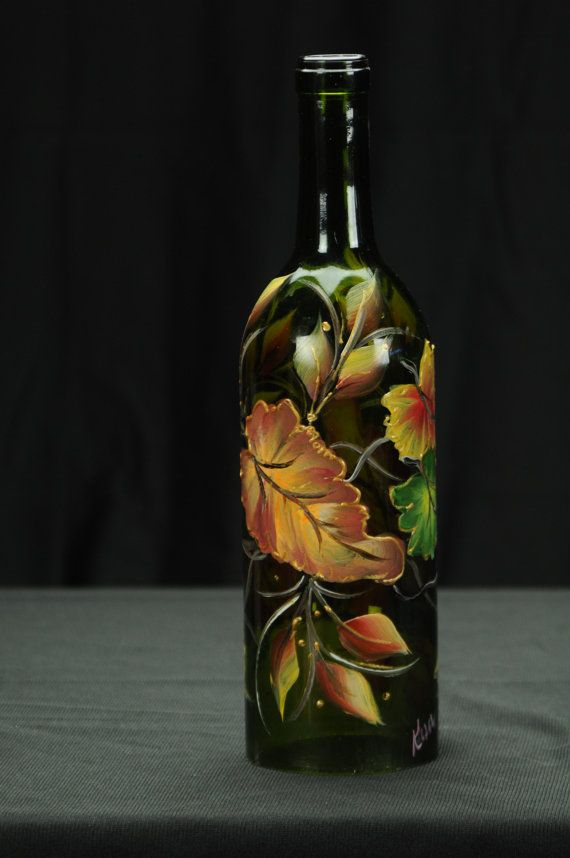 This beautiful dark brown wine bottle hurricane shade features colorful Fall Leaves. A bright and festive design that will bring a splash of color to any Autumn décor.  The bottom of the wine bottle is cut off making it possible to place it over a candle to protect it from wind and to light up the design. Photos 4 &5 show the bottle with a candle inside.  Since this bottle is painted with thermo hardened paint it is waterproof so it will do well outdoors and can also be placed in the…