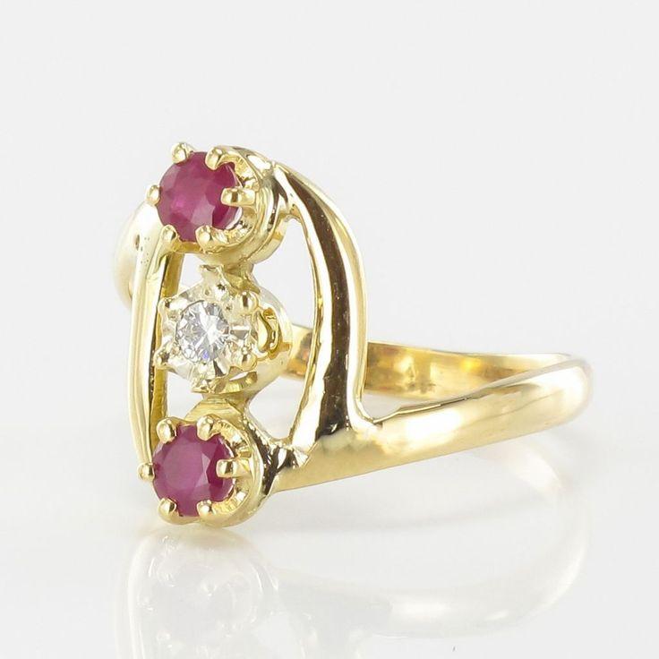 Bague rubis diamant or jaune.  Bague trilogie, elle est sertie à griffes sur son dessus de 2 rubis ronds et d'un diamant taille brillant. Le départ de l'anneau est asymétrique.  http://www.bijouxbaume.com/bague-rubis-diamant-or-jaune-a2127.html