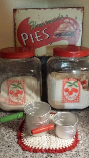Cherry glass canisters and little metal measuring cups - sweet!.
