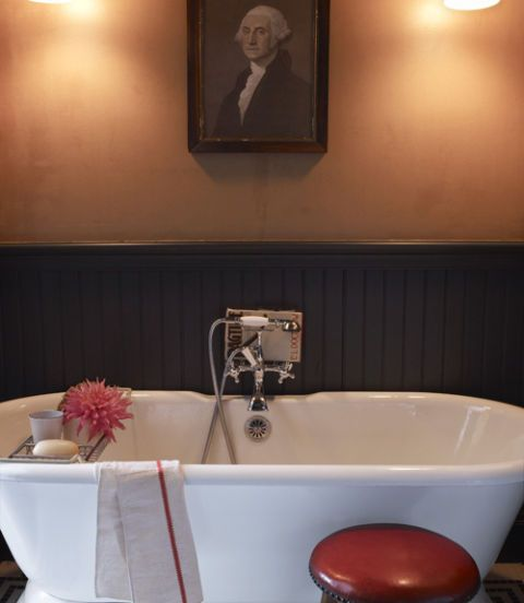 Inexpensive Kraft paper—the stuff used to cover textbooks—serves as durable wallpaper for the bathroom by adding a coat of varnish. In this photo: A Sunrise Specialty tub sits in front of beadboard painted with Benjamin Moore's black. The portrait of George Washington is a flea-market find.