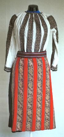 Romanian Women's costume from county of Braşov  Blouse (ie) with gathered neck (cămaşă încreţită), with a rectangular strip of black and gold embroidered across the top of the shoulder (altiţă), with vertical stripes of black and gold embroidery (râuri) on the front and sleeves.