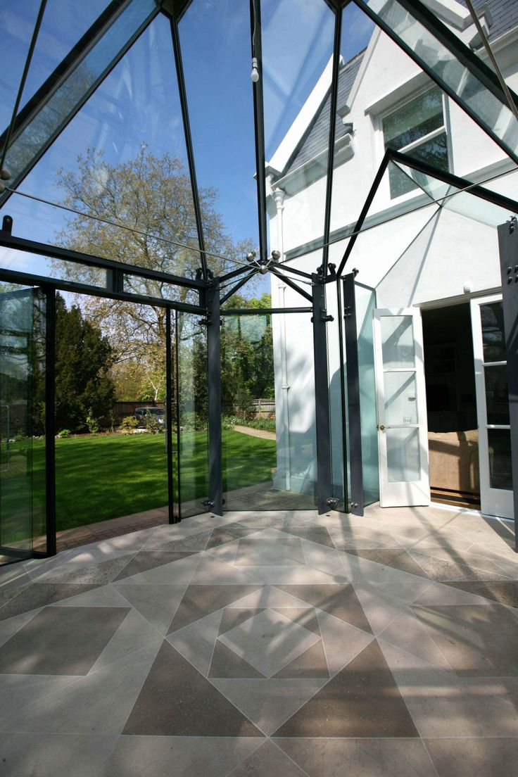 Major renovation of a listed property featuring a frameless glass conservatory with a modern, gothic design.