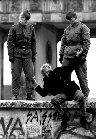 hier probeert een man te vluchten over het ijzeren gordijn, maar hij heeft pech want er staan twee soldaten hem op te wachten.