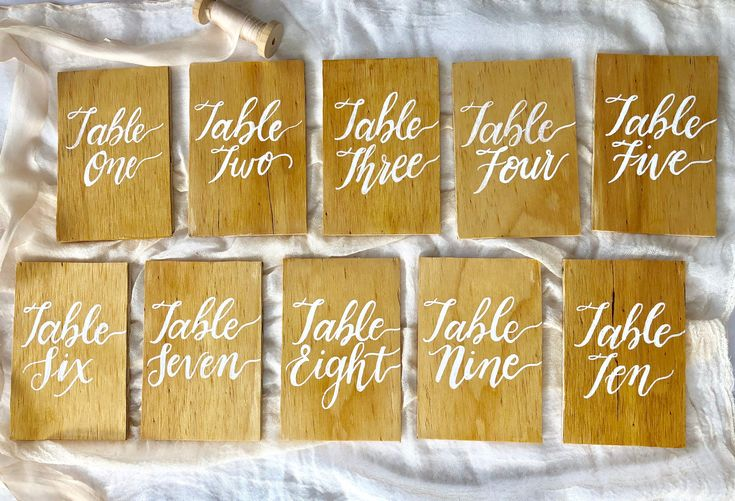 Wooden table numbers with pretty white calligraphy