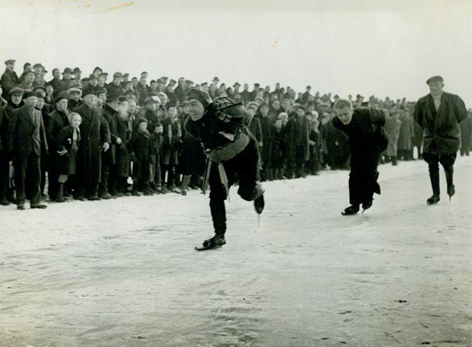 Auke Adema, begeleid door een paar onbekende schaatsers ...