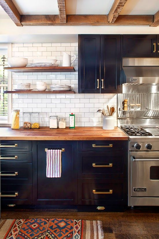 contemporary kitchen design: black cabinets, brass hardware, butcher block countertop, open shelving, subway tile