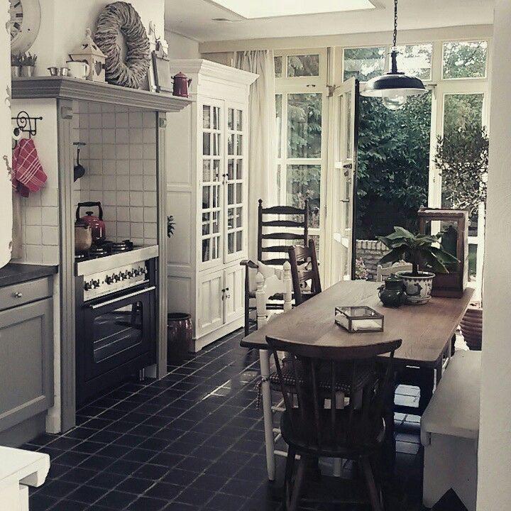 Een echte #farmhouse kitchen met hart en hout! Olijfgroene #Inbouwschouw, #houten #tafel en stoelen, oude tegelvloer, Franse #deuren en rode accenten. #vintage #kitchen #wood #olivegreen #decorating